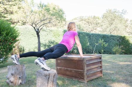 Caucasian woman doing push-ups on box and a tree trunks.Healthy lifestyle.