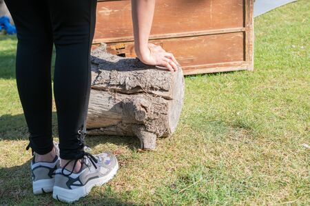 Woman leans on a tree trunk during her crossfit exercises.Healthy life and sports concept