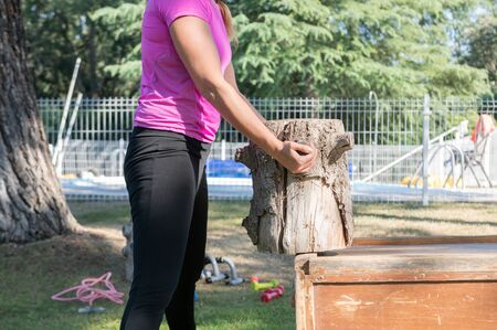 Caucasian woman holds a tree trunk that she uses in her sports routines. Healthy living and sports concept