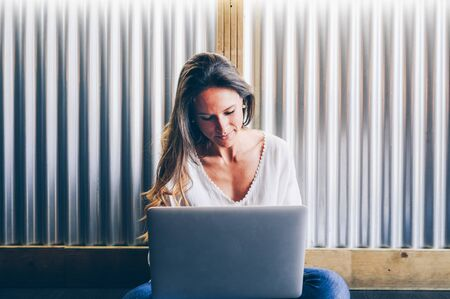 Smiling woman working on laptop while sitting on the floor with legs crossed.Copy space.Freelancer,work from everywhere concept Zdjęcie Seryjne