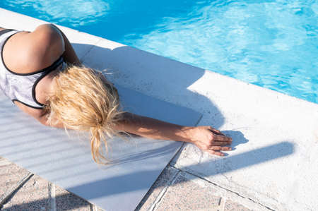 Blonde Caucasian girl relaxing by the hotel pool in a sunny day.Vacation and tourism concept
