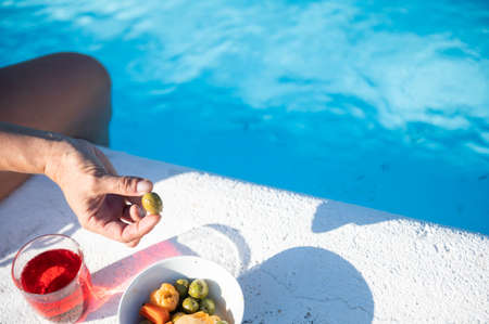 Getting your strength back with some natural snacks and a drink by the pool. Copy space.Vacations concept 스톡 콘텐츠