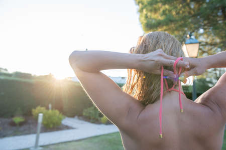 Healthy young girl ties her bikini looking at the beautiful sunset.Copy space. Enjoying the holidays