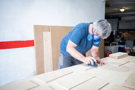 Mature carpenter wearing mask using sander while working on wood pieces.Copy space