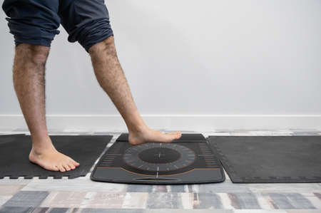 Man's foot on a pressure platform for the biomechanical study of footfall