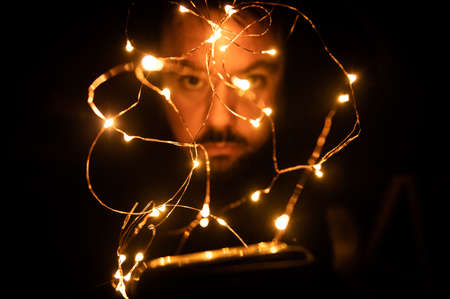 Garland of Christmas lights entangled with a young Caucasian man in an unfocused background. Stock Photo