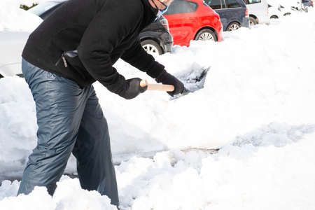 Caucasian man equipped with snow clothing and footwear helps shovel snow from a snow-covered public street.