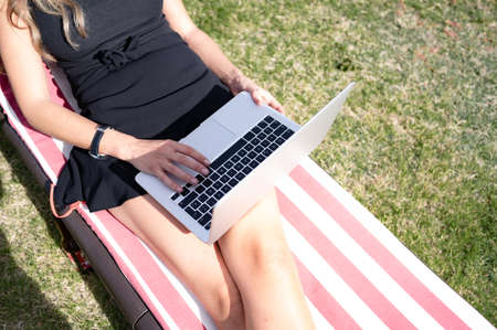 Top view of young Caucasian woman using her laptop computer relaxing in an outdoor garden. Copy space.Enjoying the life