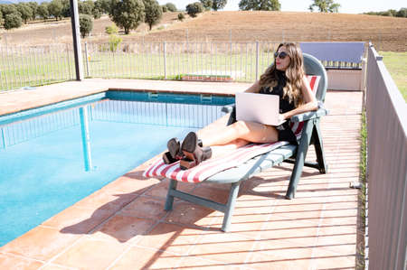 Beautiful and elegant young woman enjoying a beautiful sunny pool day holding her laptop on her lap. Enjoying life in a natural environment. Banco de Imagens