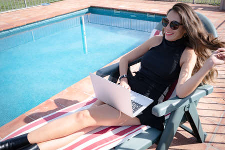 Chic pretty girl smiling holding her hair lying on a sun lounger by the pool at home on a wonderful sunny day. Enjoying life concept Banco de Imagens
