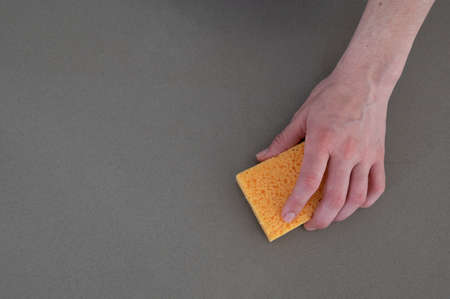 Close up of woman's hand with yellow scouring pad cleaning kitchen counter top.Copy space.Cleaning concept