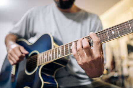 Young man practicing acoustic guitar at home.Focus selective. Stockfoto