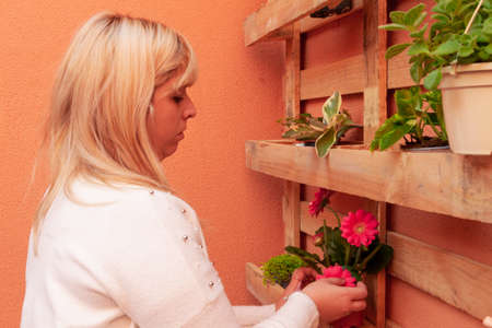 blonde woman putting pots of flowers on a pallet