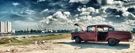 panoramic view of havana and malecon with old american car parked whit engine ploblem