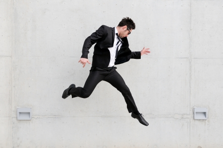 air jump: Young handsome businessman with eyeglasses jumping in the street