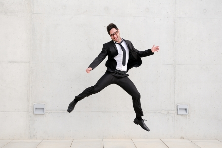 businessman jumping: Young handsome businessman with eyeglasses jumping in the street