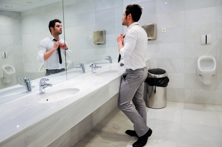 mirror on the water: Man getting dressed in a public restroom with mirror