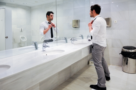 Man getting dressed in a public restroom with mirror photo