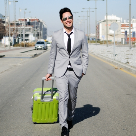 Man dressed in suit and suitcase in the street photo
