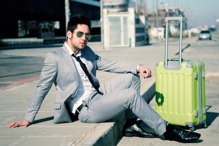Man dressed in suit and suitcase sitting on the floor in the street Stock Photo