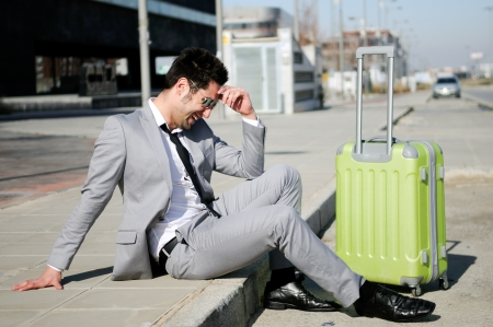 abroad: Man dressed in suit and suitcase sitting on the floor in the street Stock Photo