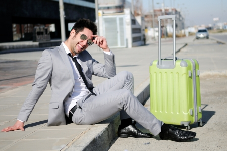 Man dressed in suit and suitcase sitting on the floor in the street Stock Photo - 16271810
