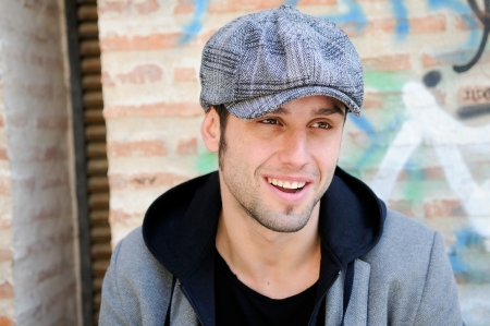 Portrait of handsome man in urban background wearing a retro cap and smiling photo