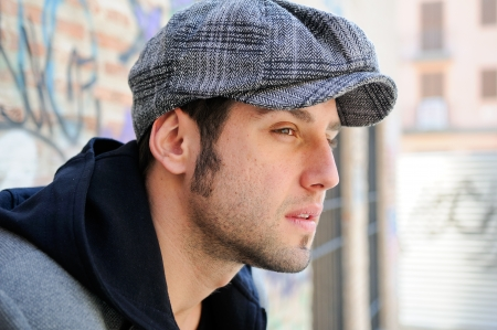 cocky: Portrait of handsome man in urban background wearing a retro cap