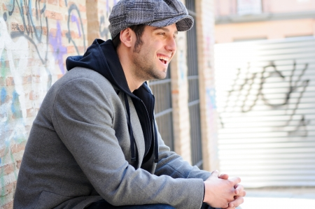 Portrait of handsome man in urban background wearing a retro cap and smiling Stock Photo