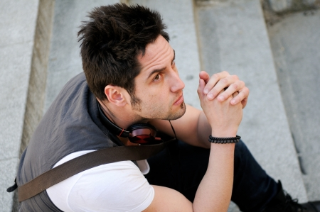 Portrait of young pensive man sitting on steps, with headphones Stock Photo - 16271780