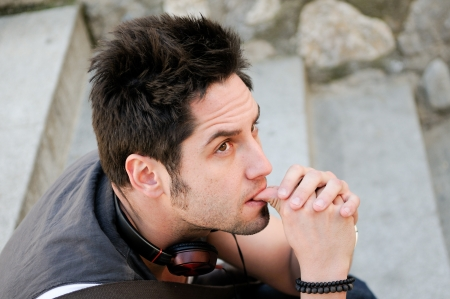 cocky: Portrait of young pensive man sitting on steps, with headphones