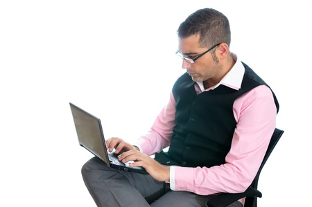 A successful businessman with glasses wearing vest and pink shirt looking at a little computer photo