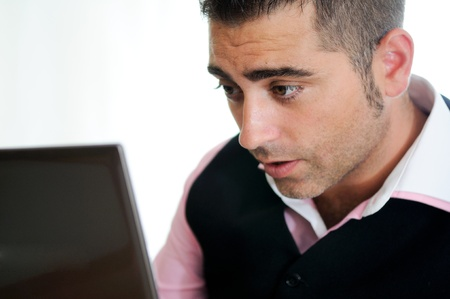 A successful businessman wearing vest and pink shirt looking at a little computer photo