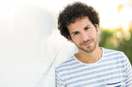 hair curly: Portrait of handsome man with curly hairstyle smiling in urban background