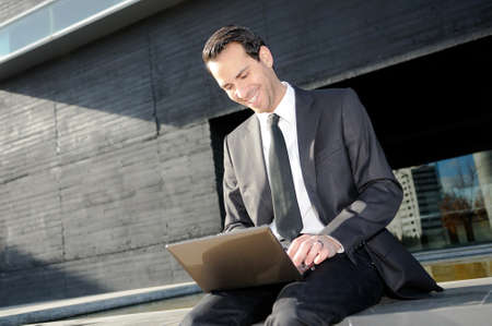 A businessman sitting on the floor with a laptop computer photo