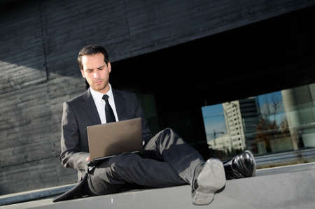 Portrait of an businessman concerned about crisis typing in a laptop computer photo