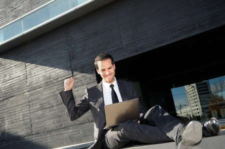 A businessman sitting on the floor with a laptop computer, rising his arm photo