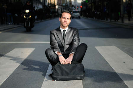 sitting on ground: Young handsome businessman sitting in a crosswalk