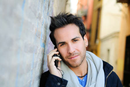 mid adult man: Portrait of handsome man in urban background talking on phone Stock Photo