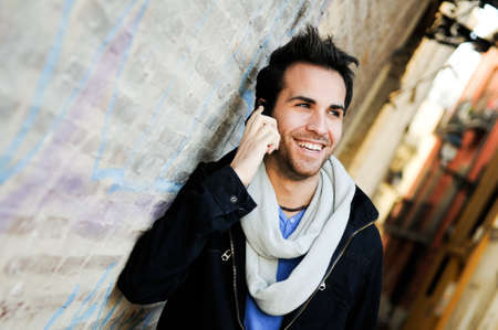Portrait of handsome man in urban background talking on phone photo