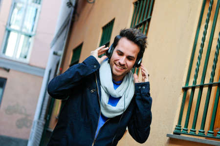 personas en la calle: Retrato del hombre hermoso en fondo urbano escuchando la m�sica con los auriculares