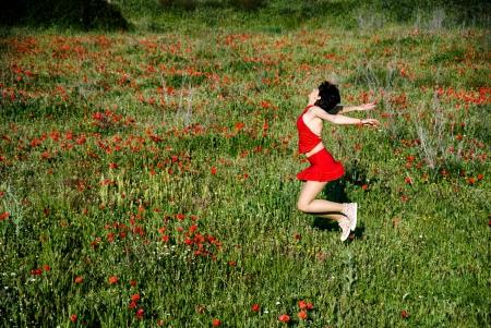Happy woman jumping in poppy field  photo