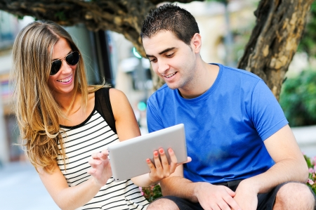 Portrait of attractive couple with tablet computer in urban background