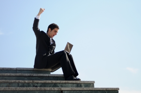 A businessman holding a laptop computer with his arm up photo