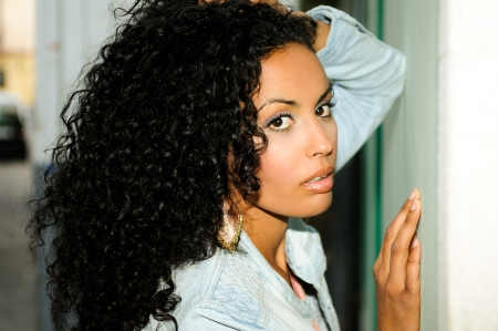 african american woman hair: Portrait of a young black woman, model of fashion in urban background Stock Photo