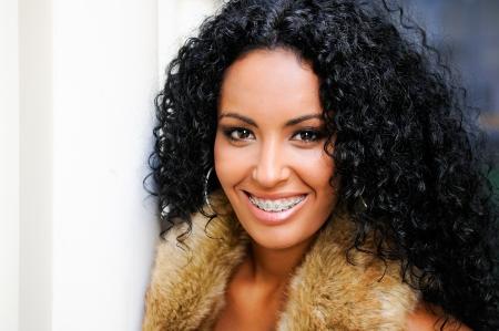 orthodontics: Retrato de una joven mujer de negro, modelo de la manera, vestido con chaleco de piel, con los apoyos