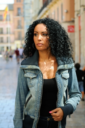 Portrait of a young black woman, model of fashion in urban background photo