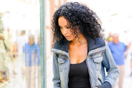 Portrait of an attractive black woman, afro hairstyle, looking at the shop window  Imagens
