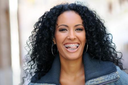 Portrait d'une jeune femme noire souriante avec bretelles