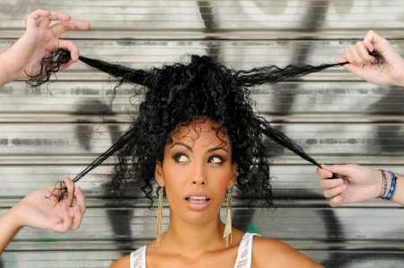 Portrait of a young black woman, afro hairstyle, in urban background with four hands playing with her hair photo